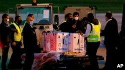 Para pekerja berdiri di samping kotak-kotak pengiriman pertama vaksin COVID-19 buatan Pfizer-BioNTech yang tiba di Bandara Internasional Rafik Hariri di Beirut, Lebanon, Sabtu, 13 Februari 2021.