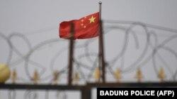 资料照片:中国国旗在新疆喀什南部地区一处建筑物的围栏铁丝网后飘扬。(2019年6月4日)