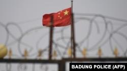 資料照片:中國國旗在新疆喀什南部地區一處建築物的圍欄鐵絲網後飄揚。 (2019年6月4日)