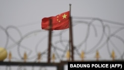 Chinese flag behind razor wire at a housing compound in Yangisar, in China's western Xinjiang region.