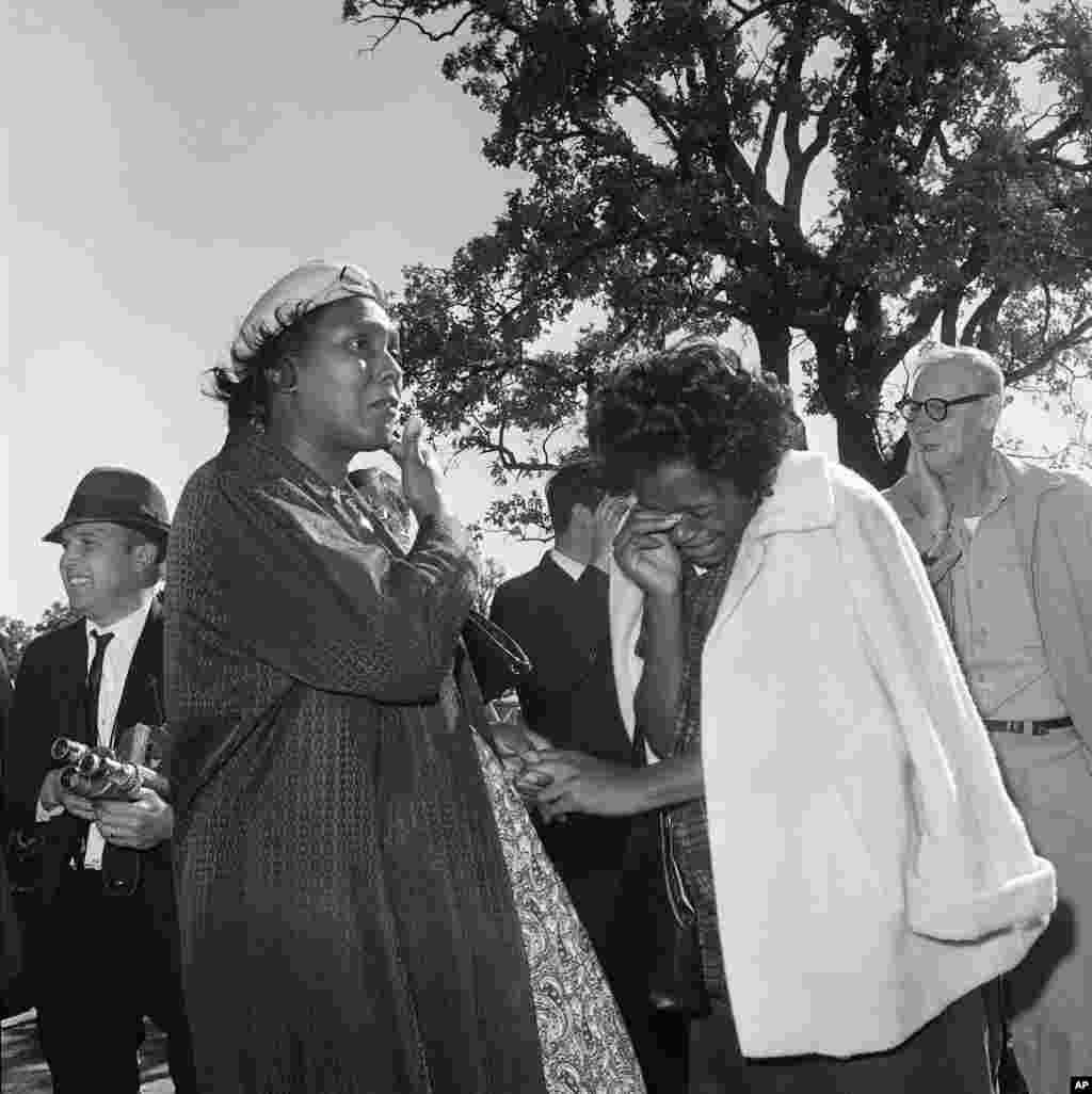 Dos mujeres rompen en llanto a las afueras del hospital Parkland al oír que el presidente Kennedy falleció del disparo que recibió mientras recorría las calles en una limosina.