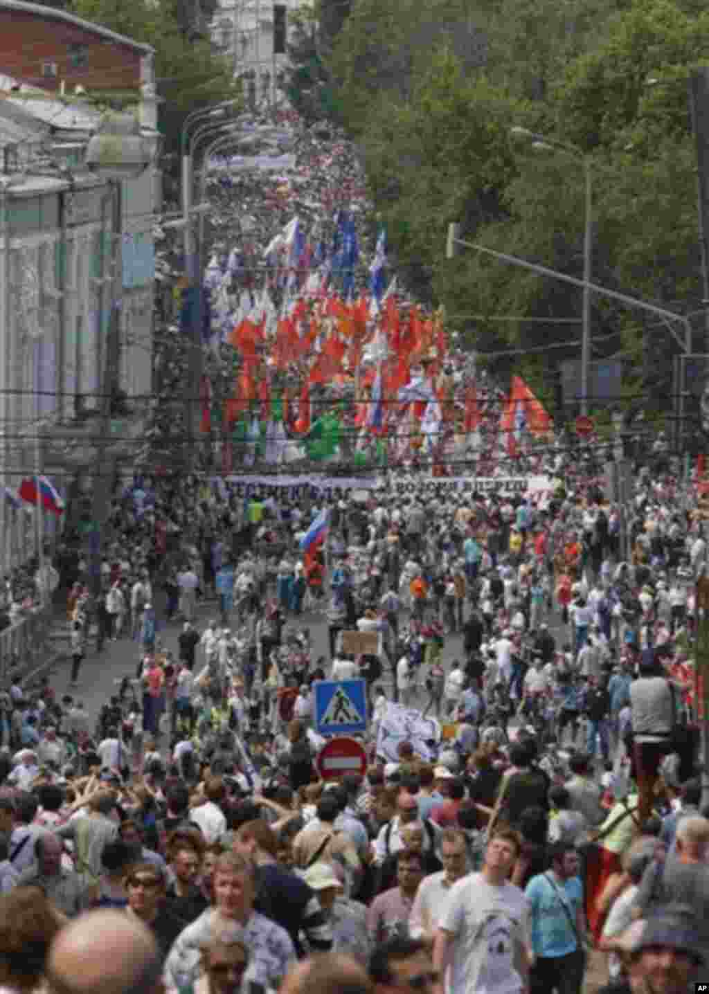 Opposition members march in central Moscow on Tuesday, June 12, 2012. Tens of thousands of Russians flooded Moscow's tree-lined boulevards Tuesday in the first massive protest against President Vladimir Putin's rule since his inauguration, as investigato