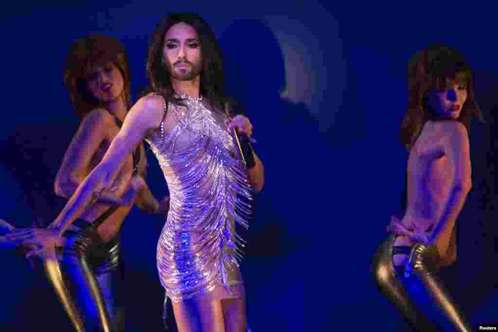 "Conchita Wurst (C), the bearded transgender winner of the Eurovision Song Contest, performs in the number ""True Love?"" on stage with topless dancers during a rehearsal for the show ""Desirs"" at the Crazy Horse cabaret in Paris, Oct. 30, 2014."