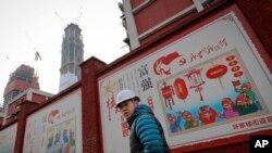 建筑工人走过北京一个居民小区外面,墙上有宣传牌《社会主义核心价值观:富强》《社会主义核心价值观:民主》(资料照片)