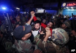 Lebanese soldiers arrest a suspected attacker near the scene of a twin suicide attack in Burj al-Barajneh, a predominantly Shi'ite suburb of southern Beirut, Lebanon, Nov. 12, 2015.