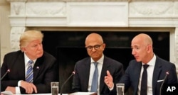 FILE - President Donald Trump, left, and Satya Nadella, Chief Executive Officer of Microsoft, center, listen as Jeff Bezos, Chief Executive Officer of Amazon, speaks during an American Technology Council roundtable in the State Dinning Room of the White House, June 19, 2017.
