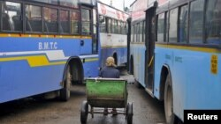 FILE - A porter sits in his pushcart as he waits for customers in between passenger buses at a municipal bus terminal in Bengaluru, India, Sept. 8, 2015. The first bus of its kind hit the streets of the Indian capital, New Delhi, Wednesday equipped with safety features to increase security for women.