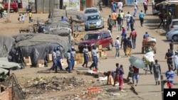 La police anti-émeute patrouille près d'un marché très fréquenté malgré le confinement à Harare au Zimbabwe, le 7 avril 2020.