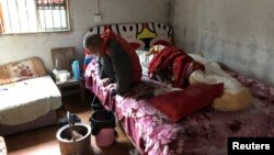 FILE - Wang Zhaohong, who suffers from silicosis, is seen on his bed in Sangzhi county, Hunan province, China, Nov. 27, 2018.