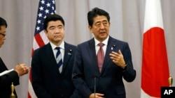 ນາຍົກລັດຖະມົນຕີຍີ່ປຸ່ນ ທ່ານ Shinzo Abe (ຂວາ) ຕອບຄຳ ຖາມບັນດາສື່ມວນຊົນ.