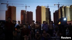 Migrant construction workers watch an open air movie near their dormitories after a shift at a residential construction site in Shanghai, July 15, 2013.