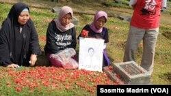 Pendamping, keluarga korban dan korban saat berziarah sambil melakukan tabur bunga di TPU Pondok Ranggon, Jakarta, Senin, 13 Mei 2019. (Foto: Sasmito Madrim/VOA)