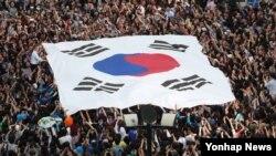 4일 한국 고양시 일산 문화공원에서 열린 대선후보 집중유세 현장에서 시민들이 대형태극기를 들어보이고 있다.