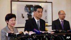 星期四舉行的記者會上的香港政務司司長林鄭月娥(左)特首梁振英(中)和政制及內地事務局局長譚志源(右)。
