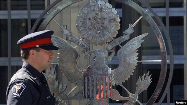 FILE - A police officer patrols the United States embassy in Ottawa, Canada.