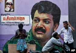 """FILE - People stand in front of a mural of Sri Lanka's Liberation Tigers of Tamil Eelam (LTTE) leader Velupillai Prabhakaran painted on a wall in Chennai, India, May 19, 2015. Across Chennai, large billboards with photographs of Prabhakaran, the leader of the Tamil Tigers, urge its people to """"not forget"""" the day the insurgent group accepted defeat."""
