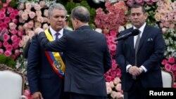 El nuevo presidente de Colombia, Iván Duque, recibe la banda presidencial del presidente del Senado, Ernesto Macías, durante su ceremonia de inauguración en la Plaza Bolívar, en Bogotá, Colombia, el 7 de agosto de 2018. REUTERS / Carlos Garcia Rawlins -
