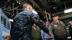 Presidente Donald Trump saluda al oficial de primera clase, John Thompson durante su visita al portaaviones Gerald R. Ford.