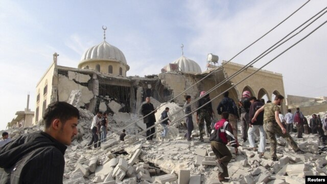 Residents and members of the Free Syrian Army inspect Bilal mosque, which activists said was damaged after it was fired upon by a Syrian Air Force fighter jet loyal to Syria's President Bashar al-Assad, at Marat al-Numan near the northern province of Idli