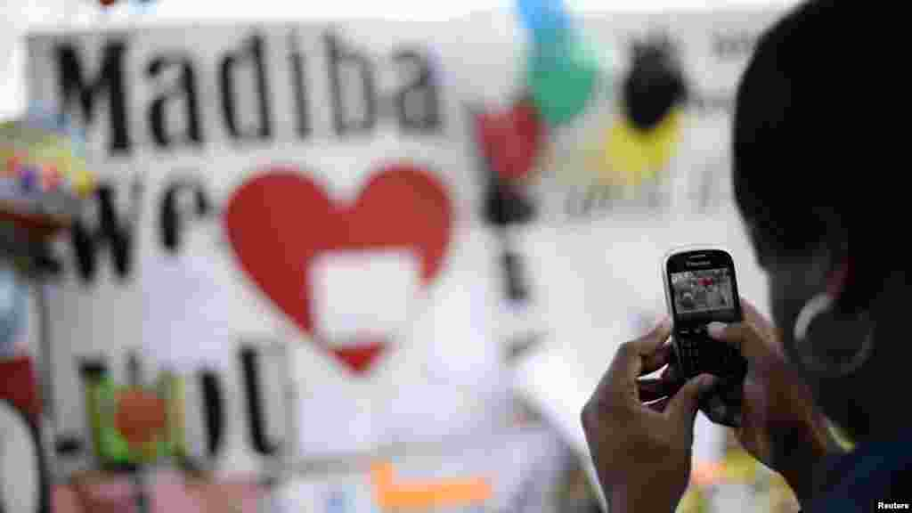 A woman takes a photograph outside the hospital where ailing former President Mandela is being treated.