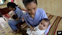 Anak-anak bayi Vietnam yang siap untuk diadopsi bersama pengasuhnya (foto: dok).