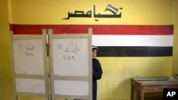A woman prepares to vote during the second day of the presidential election at a polling station in Cairo, Egypt, Tuesday, March 27, 2018. Egyptians are voting for a second day in a lackluster election that President Abdel-Fattah el-Sissi is virtually certain to win after all serious rivals were either arrested or intimidated into dropping out ahead of the balloting.