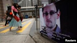 A poster supporting Edward Snowden, a former contractor at the National Security Agency who leaked revelations of U.S. electronic surveillance, is displayed at Hong Kong's financial Central district June 17, 2013.