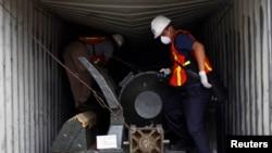 """巴拿马有关工作人员手握""""清川江号""""船只上被查扣的一件绿色的导弹部件。"""