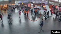 吉隆坡国际机场的监控录像显示一名据信是金正男的男子(圆圈内)在与机场工作人员交谈。(2017年2月13日)