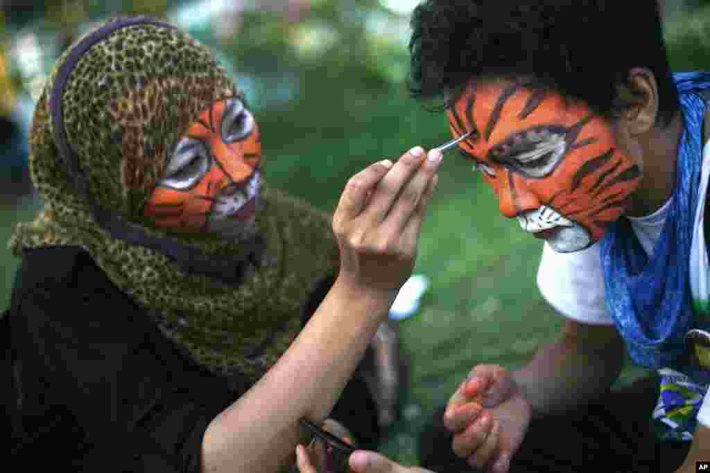 Students paint their faces during a rally calling for Sumatran tiger conservation ahead of the Global Tiger Day in Medan, North Sumatra, Indonesia. The Sumatran tiger is the world's most critically endangered tiger subspecies with only fewer than 400 remain in the wild and may become extinct in the next decade due to poaching and habitat loss.