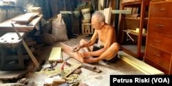 Seorang warga lansia yang tinggal di kampung pecinan Tambak Bayan, Surabaya, sedang membuat perabotan dari kayu, Surabaya, Jawa Timur, 28 Agustus 2019. (Foto: Petrus Riski/Terkini.com)