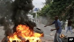 A Haitian throws a tire into fire during a protest following presidential elections in Port-au-Prince, 8 Dec 2010