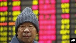 Seorang investor di depan layar monitor harga saham di sebuah perusahaan sekuritas swasta di Shanghai. (Foto: Ilustrasi)