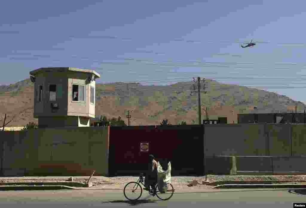 A NATO helicopter flies overhead at the site of a suicide attack outside the counter-narcotics office near the Kabul International Airport, July 22, 2014.