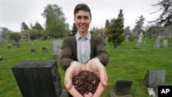 FILE - Katrina Spade, the founder and CEO of Recompose, a company that hopes to use composting as an alternative to burying or cremating human remains, poses for a photo in a cemetery in Seattle as she displays a sample of compost material left from the d