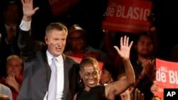 纽约市民主党市长候选人比尔•德•布拉西奥(左)与夫人9月11日在党内初选结束后在竞选总部向支持者挥手致意。
