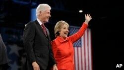 Mantan Presiden AS Bill Clinton dan isterinya, Hillary Rodham Clinton, kandidat capres dari partai Demokrat AS, melambaikan tangan kepada para pendukungnya pada malam penggalangan dana di Des Moines, Iowa (24/10).