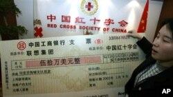 中国红十字会的雇员举着中国电脑公司联想集团捐助的50万美元支票的放大版本(资料照片)