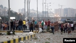 ພວກຕໍ່ຕ້ານ ທ່ານ Mohamed Morsi ປະທານາທິບໍດີ ທີ່ຖືກໂຄ່ນລົ້ມຂອງອີຈິບ ແກວ່ງກ້ອນຫີນໃສ່ພວກສະໜັບສະໜຸນ ໃນລະຫວ່າງການປະທະກັນ ທີ່ຄຸ້ມ Nasr ໃນກຸງໄຄໂຣ (27 ກໍລະກົດ 2013)