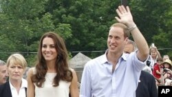 Britain's Prince William waves to spectators while walking with his wife Catherine, Duchess of Cambridge, at Fort Levis in Levis, Quebec July 3, 2011.