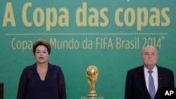 Presiden Brazil Dilma Rousseff (kiri) dan Presiden FIFA Joseph Blatter dalam upacara penyerahan trofi Piala Dunia 2014 di istana presiden Planalto di Brasilia, Brazil (2/6). (AP/Eraldo Peres)
