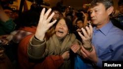 Un pariente de uno de los pasajeros chinos del vuelo MH370 llora al escuchar las noticias de que el avión desaparecido se estrelló en el mar.