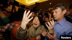 Seorang anggota keluarga penumpang Malaysia Airlines penerbangan MH370 menangis setelah melihat konferensi pers pemerintah Malaysia di hotel Lido, Beijing (24/3). (Reuters/Jason Lee)
