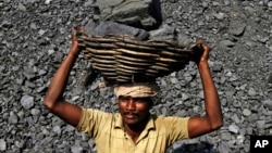 FILE - an Indian daily wage laborer carries a basket on his head filled with chunks of coal at a local coal depot on the outskirts of Cuttack, India, Nov. 13, 2014.