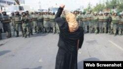 资料照:一名新疆维吾尔妇女举拳向一队中国武警士兵表示抗议。(照片来自世界维吾尔代表大会网站)