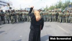 資料照:一名新疆維吾爾婦女舉拳向一隊中國武警士兵表示抗議。 (照片來自世界維吾爾代表大會網站)