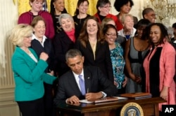 FILE - President Barack Obama signs executive actions, with pending Senate legislation, aimed at closing a compensation gender gap that favors men during an event in Washington marking Equal Pay Day, April 8, 2014.