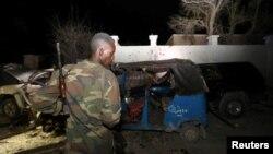 2016年8月25日一名索马里警察在查看在海滩餐厅汽车炸弹中摧毁了的车辆的残骸。