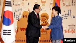 Presiden Laos Choummaly Sayasone (kiri) berjabat tangan dengan Presiden Korea Selatan Park Geun-hye saat tiba di Istana Presiden di Seoul (22/11). (Reuters/Lee Jin-man/Pool)