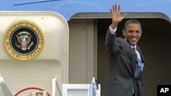 President Barack Obama waves from the top of the steps of Air Force One at Andrews Air Force Base, on his way to Martha's Vineyard for vacation, Aug. 18, 2011